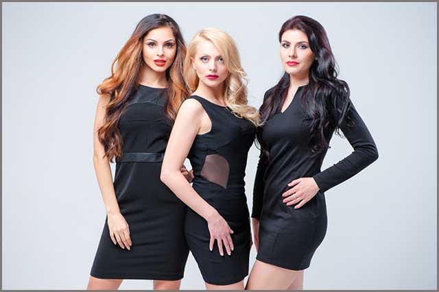 Three women posing in black dresses