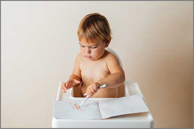 A toddler playing with papers