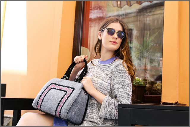 A stylish young woman carrying a felt bag